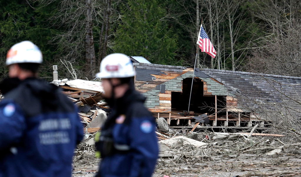 . Searchers stand in view of several destroyed homes as they wait to begin looking through the debris of a mudslide Tuesday, March 25, 2014, in Oso, Wash. (AP Photo/Elaine Thompson)