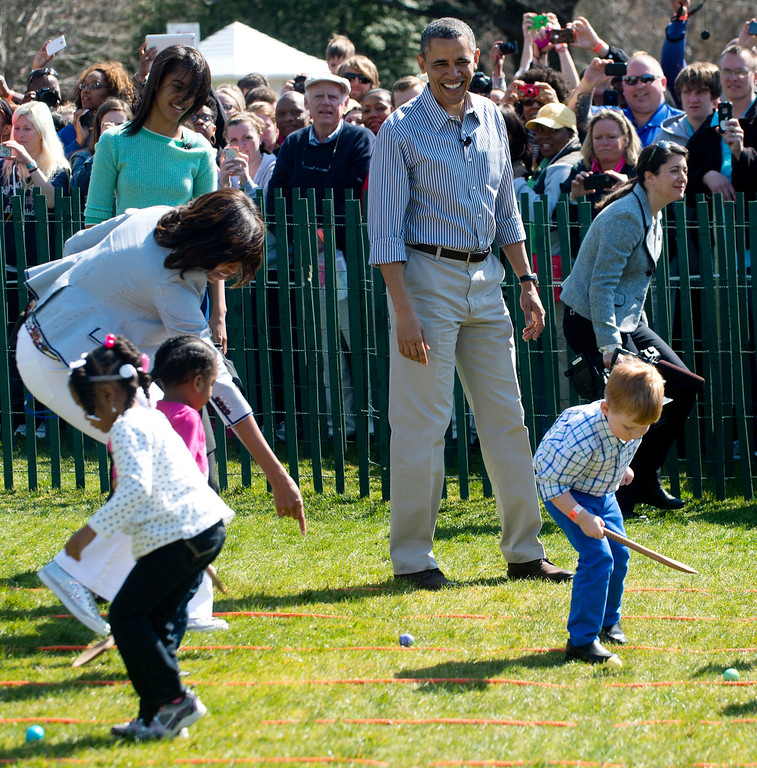 . US President Barack Obama (C) and First Lady Michelle Obama (L) cheer children as they race to roll eggs as they participate in the White House Easter Egg Roll on the South Lawn of the White House in Washington, DC, April 1, 2013. Obama hosts the annual event, featuring live music, sports courts, cooking stations, storytelling and Easter egg rolling. AFP PHOTO / Saul LOEB/AFP/Getty Images