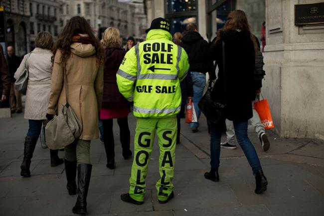 . A man advertises a golf sale on Regent Street in London, Wednesday, Feb. 20, 2013. (AP Photo/Matt Dunham)
