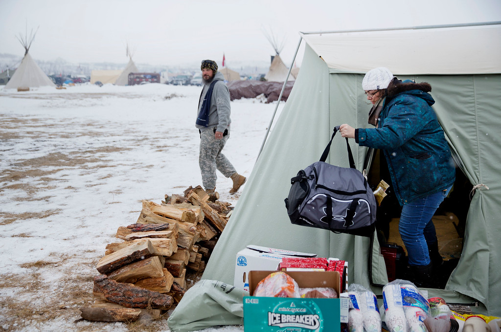 . U.S. Navy veteran Wendy Drey, right, of Citrus Hill, Calif., comes out of a tent as she packs up to leave the Oceti Sakowin camp where people have gathered to protest the Dakota Access oil pipeline in Cannon Ball, N.D., Monday, Dec. 5, 2016. Drey\'s tent does not have a wood floor or a wood stove which are considered necessary to ride out the upcoming wintry weather. Some in her camp decided to leave while others planned on staying and making the recommended changes to their sleeping arrangements. (AP Photo/David Goldman)