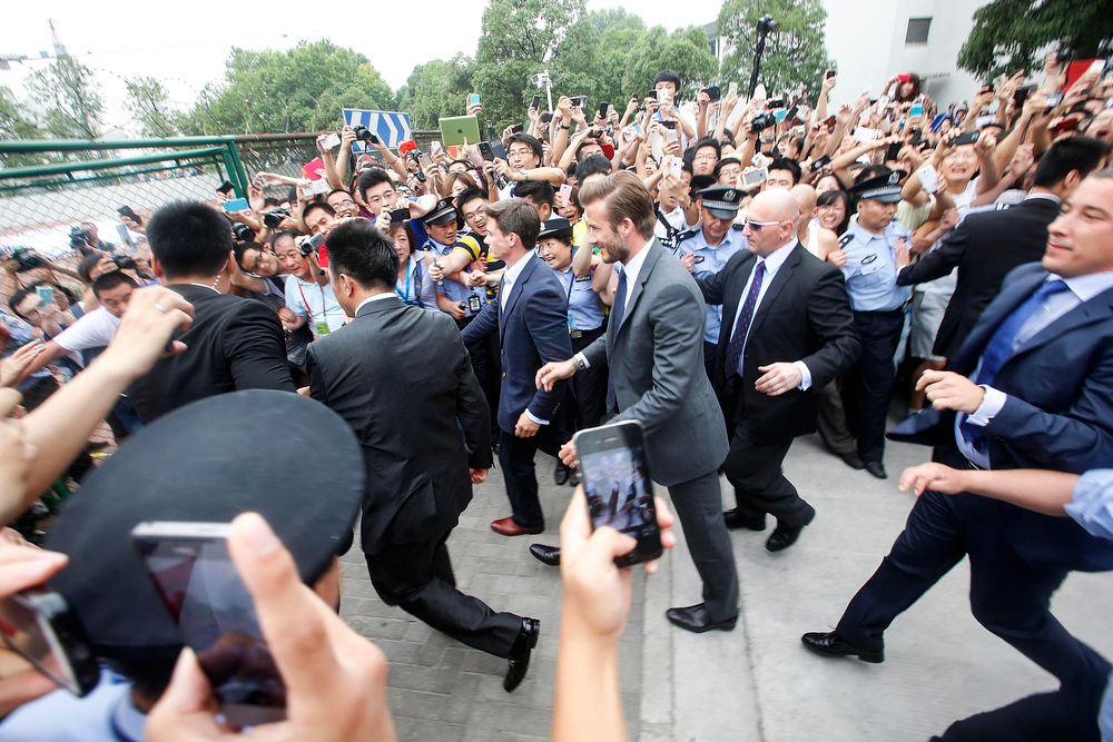 . Fans push towards policemen as they take pictures and videos of former England soccer captain David Beckham upon his arrival at Tongji University, in Shanghai June 20, 2013. Beckham cancelled his event at Tongji University after a stampede accident happened upon his arrival injuring at least five people on Thursday, local media reported. REUTERS/Stringer