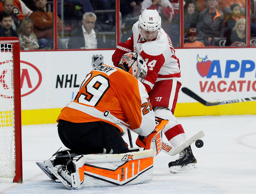 . Philadelphia Flyers\' Ray Emery (29) left, defends the goal as Detroit Red Wings\' Gustav Nyquist (14) is unable score in the third period of an NHL hockey game Saturday, Oct. 25, 2014, in Philadelphia. The Flyers won 4-2. (AP Photo/Tom Mihalek)