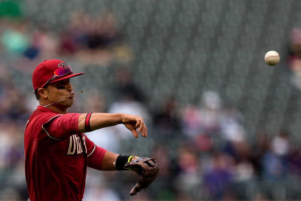 . DENVER, CO - APRIL 6:  Third baseman Martin Prado #14 of the Arizona Diamondbacks throws to first base for the final out of the first inning against the Colorado Rockies at Coors Field on April 6, 2014 in Denver, Colorado.  (Photo by Justin Edmonds/Getty Images)