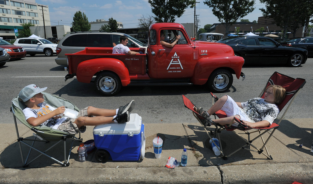 . Kole Gonzales, left, age 11, and his friend, Liam Hall, age 12, of Auburn Hills, Mich., relax in their chairs as they watch cruisers head southbound on Woodward, south of Maple Road.  Photo taken during the Woodward Dream Cruise on Saturday, August 15, 2009, in Birmingham, Mich.  (The Oakland Press/Jose Juarez)
