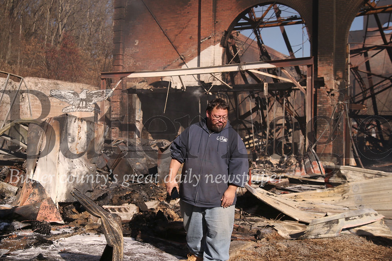 Joe Sharon of Pittsburgh walks through the wreckage of the 'man cave' worshop space he and Rob Goupil rented to restore classic cars. Spared from the initial Friday night fire, Sharon's space caught fire in a second blaze Saturday morning, likely sparked by remaining hotspots from the previous night's fire that destroyed the old glass factory, now comercial space, in Renfrew. Seb Foltz/Butler Eagle