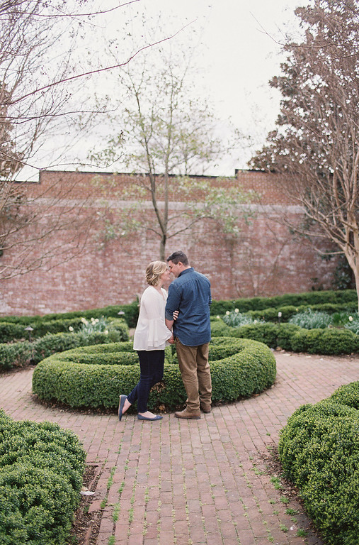 Lauren and Ty's Old Town Alexandria engagement photos included a stop in a garden to shoot by some boxwood bushes.