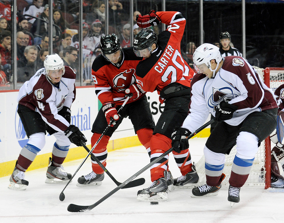 . Colorado Avalanche\'s Erik Johnson, right, and Tyson Barrie, left, battle for control of the puck against New Jersey Devils\' Ryan Carter (20) and Steve Bernier during the second period of an NHL hockey game, Monday, Feb. 3, 2014, in Newark, N.J. (AP Photo/Bill Kostroun)