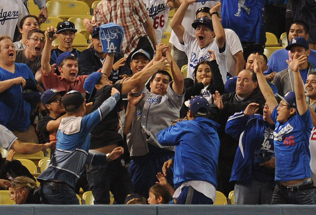 . Fans battle for the game winning home run ball. The Dodgers defeated the Arizona Diamondbacks 5-3 after Scott Van Slyke hit a 2 run walk off homer in the 11 inning at Dodger Stadium in Los Angeles, CA. 9/10/2013. photo by (John McCoy/Los Angeles Daily News)