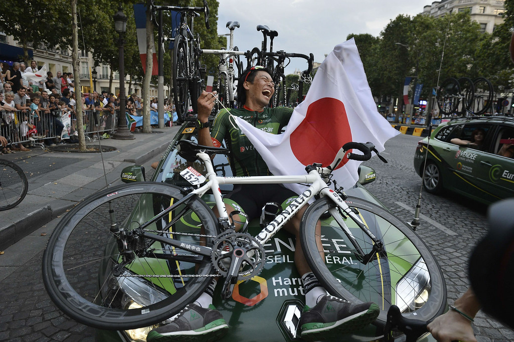 . Japan\'s Yukiya Arashiro parades on the Champs-Elysees avenue in Paris with a Japanese national flag, at the end of the 137.5 km twenty-first and last stage of the 101st edition of the Tour de France cycling race on July 27, 2014 between Evry and Paris.    JEFF PACHOUD/AFP/Getty Images