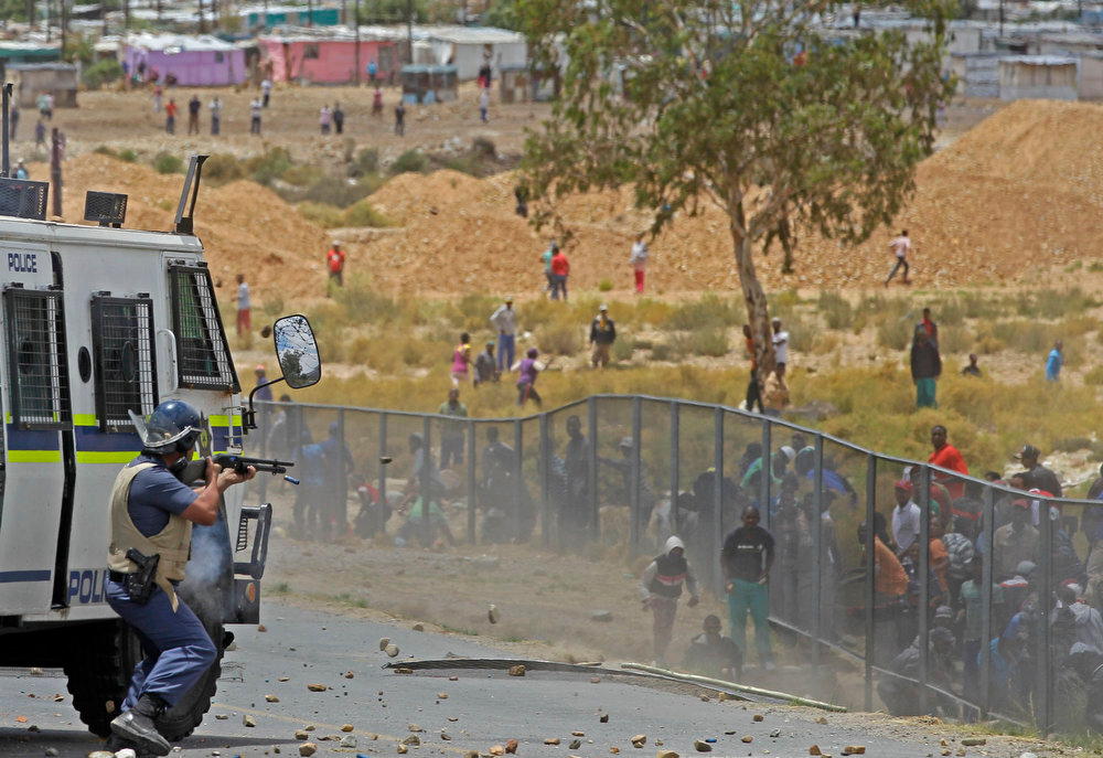 Description of . A South African policeman. left,  fire's a rubber bullet, at striking farm workers as they demonstrate in De Doorns , South Africa, Thursday, Jan 10, 2013. Striking farm workers in South Africa have clashed with police for a second day during protests for higher wages. The South African Press Association says police on Thursday fired rubber bullets at rock-throwing demonstrators in the town of De Doorns in Western Cape province, and protests were occurring in at least two other towns. (AP Photo/Schalk van Zuydam)