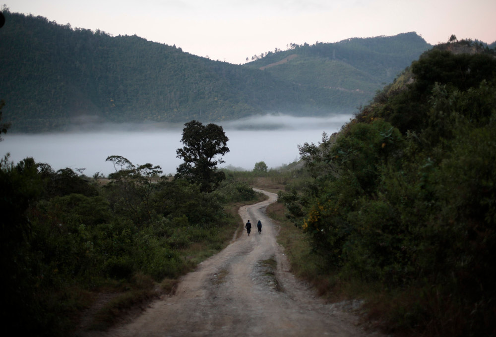 Description of . Two men walk, in the morning, along the road to Chicoy, in the Alta Verapaz region, some 180km, (110 miles), from Guatemala City, December 20, 2012. This week, at sunrise on Friday, December 21, an era closes in the Maya Long Count calendar, an event that has been likened by different groups to the end of days, the start of a new, more spiritual age or a good reason to hang out at old Maya temples across Mexico and Central America. REUTERS/Jorge Dan Lopez