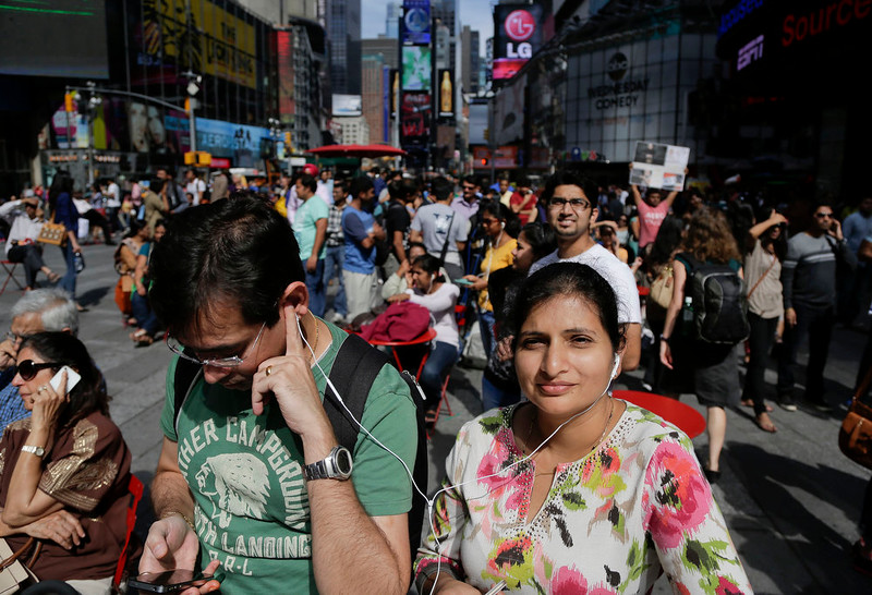 . A couple shares a set of headphones as they gather in Times Square with other members of the Indian-American community to watch a live stream of Indian Prime Minister Narendra Modi speaking to a capacity crowd at Madison Square Garden, Sunday, Sept. 28, 2014, in New York. A day after addressing a hushed U.N. General Assembly, where headphone-wearing delegates rarely break into a smile, India\'s new prime minister told a packed and boisterous crowd to help him develop his nation\'s economy, vowing that under his leadership, India won\'t look back. (AP Photo/Julie Jacobson)