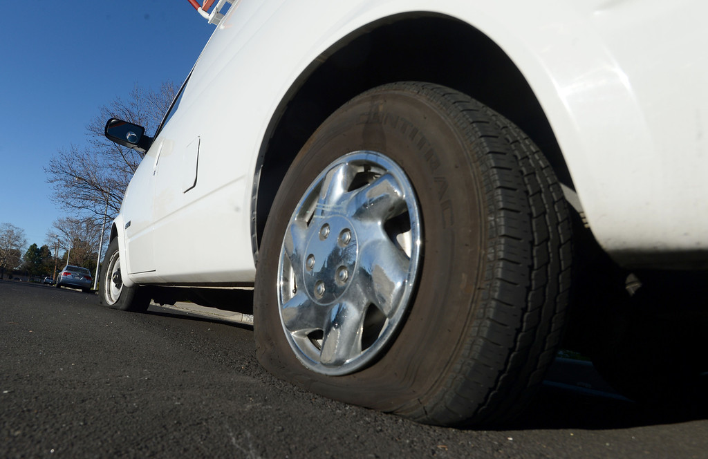 . Flat tires are a common sight along Glazier Drive in Concord, Calif., on Monday, Feb. 11, 2013, where two white service vans had all the tires slashed over the weekend. Concord police officers found tires slashed on about 60 vehicles. (Susan Tripp Pollard/Staff)