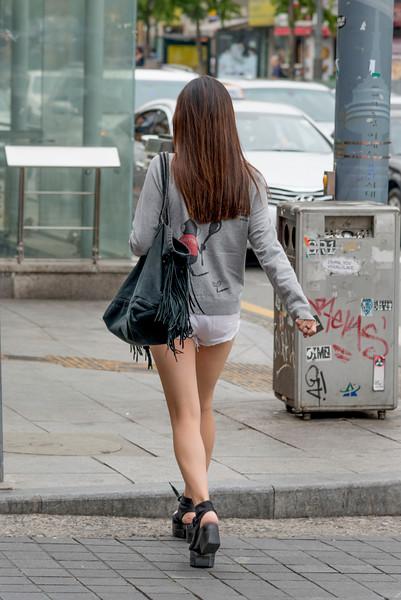 Woman walking on sidewalk, Seoul, South Korea