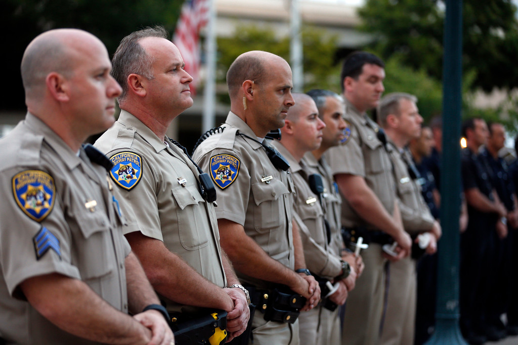 . Officers from the California Highway Patrol stand together during a candlelight vigil for slain Hayward police Sgt. Scott Lunger at Hayward City Hall in Hayward, Calif., on Wednesday, July 22, 2015. Lunger was killed during a traffic stop early Wednesday. (Ray Chavez/Bay Area News Group)