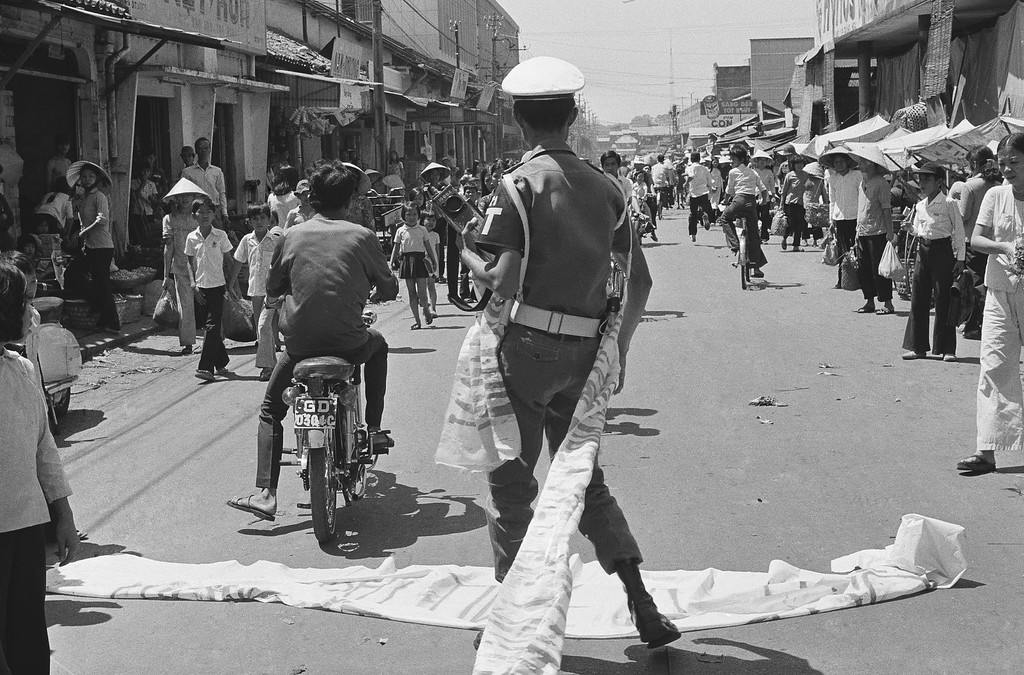. A Saigon student demonstrator hastily flees after a policeman grabbed his antigovernment banner, Thursday, April 9, 1975. About 30 students protested the draft and demanded the ouster of South Vietnamese President Nguyen Van Thieu. (AP Photo/Dang Van Phuoc )
