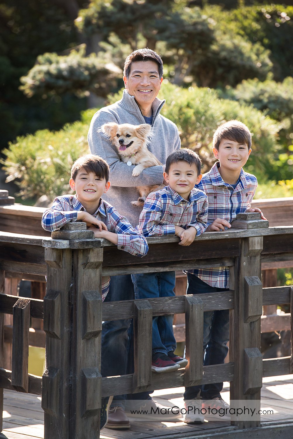father in gray sweater and three boys in gray shirts on the wood bridge at Hayward Japanese Garden