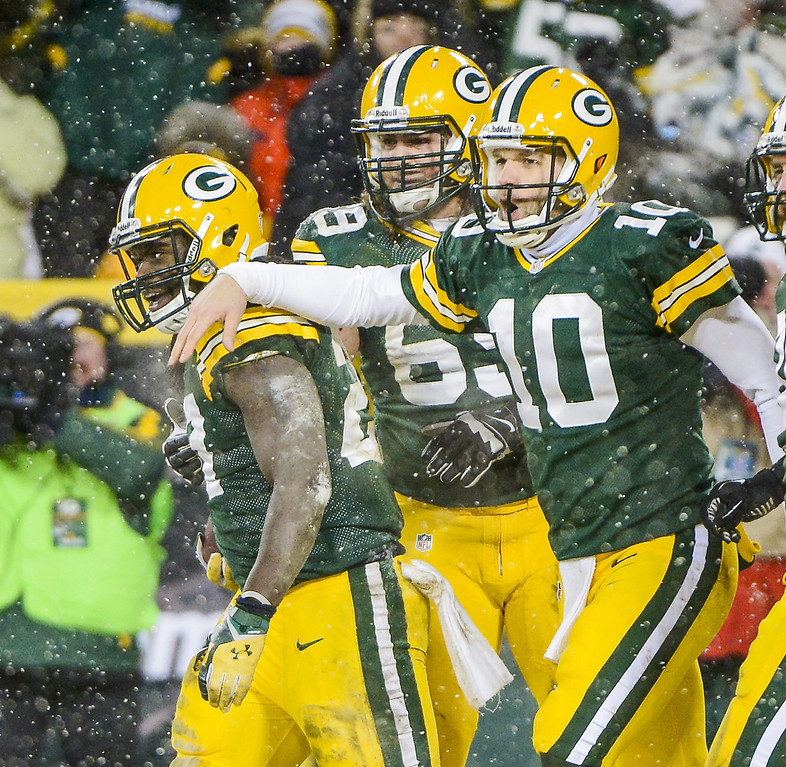 . Green Bay Packers offensive player Eddie Lacy (L) celebrates scoring a touchdown with Green Bay Packers quarterback Matt Flynn (R) and Green Bay Packers offensive player David Bakhtiari (C) as snow falls in the first half of their NFL game at Lambeau Field in Green Bay, Wisconsin, USA, 22 December 2013.  EPA/TANNEN MAURY