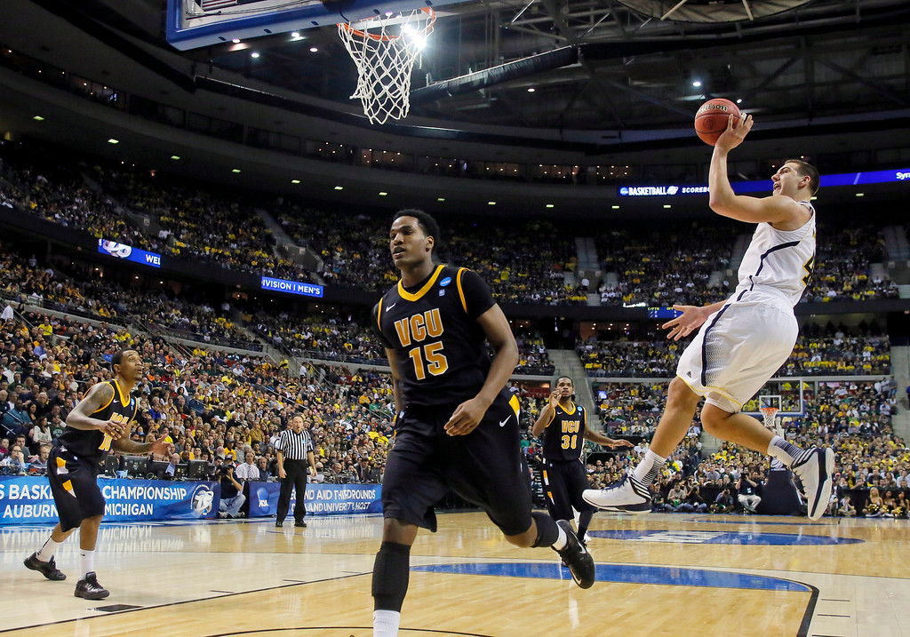 . Michigan forward Mitch McGary (4) takes a shot as Virginia Commonwealth forward Juvonte Reddic (15) overruns the play in the second half of a third-round game of the NCAA college basketball tournament Saturday, March 23, 2013, in Auburn Hills, Mich. (AP Photo/Duane Burleson)