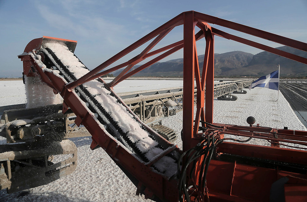 . Salt is collected at a production site in Messolongi, western Greece, on Monday Sept. 30, 2013. Salt lakes at Messolongi are used for production by solar evaporation. The facilities are the largest saltworks in Greece, and are located at a protected wetland complex of estuaries and lagoons. (AP Photo/Dimitri Messinis)