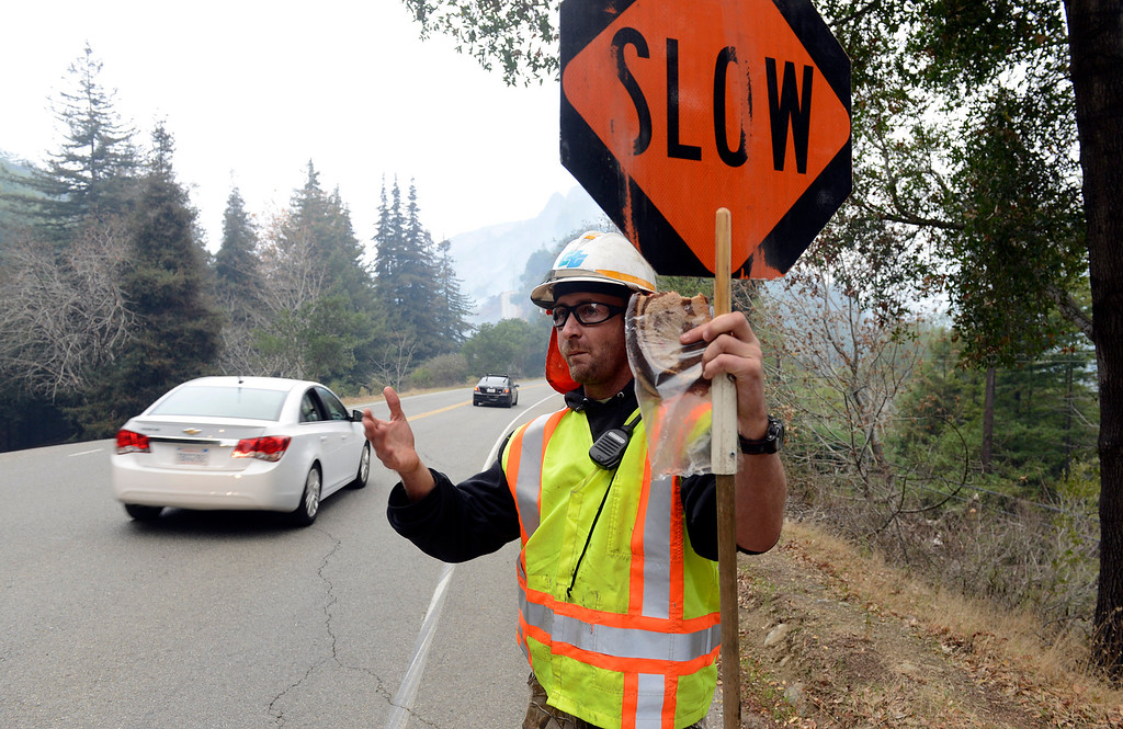 . A CalTrans worker eats his lunch while directing traffic through the backfire along Highway 1 in Big Sur, Calif. on Wednesday December 18, 2013. (Photo David Royal/ Monterey County Herald)