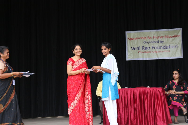 Mrs. Ratna Reddy, Founder Trustee- Veni Rao Foundation giving scholarship cheque to Ms. Kasimbee.JPG