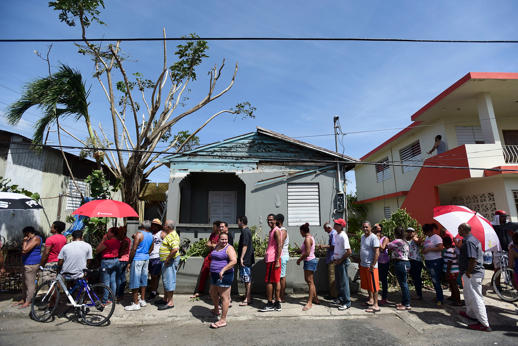 . People affected by the passage of Hurricane Maria wait in line at Barrio Obrero to receive supplies from the national Guard, in San Juan, Puerto Rico, Sunday, Sept. 24, 2017. Federal aid is racing to stem a growing humanitarian crisis in towns left without fresh water, fuel, electricity or phone service by the hurricane. (AP Photo/Carlos Giusti)