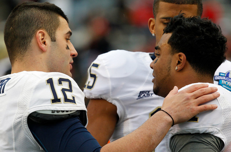 . Pittsburgh quarterback Tino Sunseri (12) tries to console running back Rushel Shell (4) on the sidelines during the second half of their 38-17 loss to Mississippi in the BBVA Compass Bowl NCAA college football game on Saturday, Jan. 5, 2013, in Birmingham, Ala. (AP Photo/Butch Dill)
