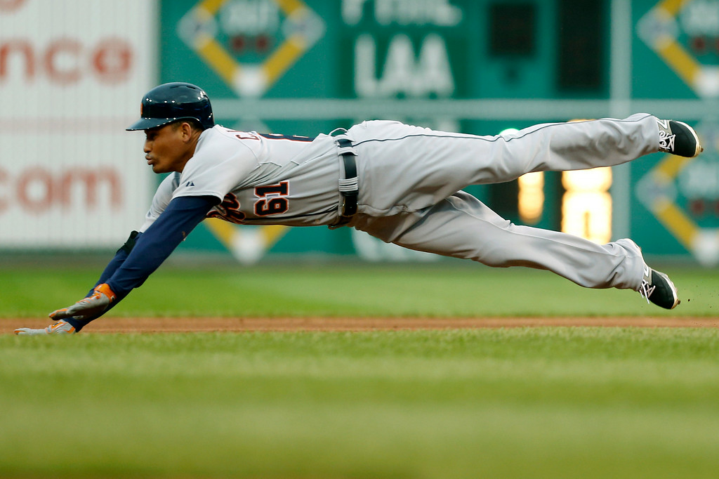 . Detroit Tigers\' Ezequiel Carrera (61) dives for second base with a double in the first inning of the baseball game against the Pittsburgh Pirates on Tuesday, Aug. 12, 2014, in Pittsburgh. Carrera then scored on a hit by Ian Kinsler that inning. (AP Photo/Keith Srakocic)