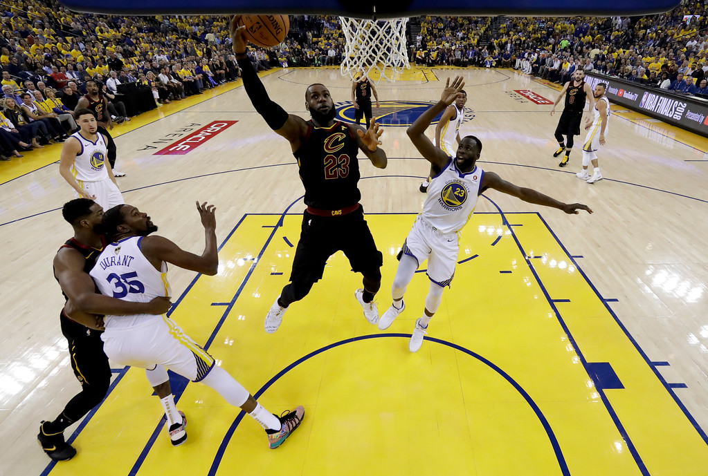 . Cleveland Cavaliers forward LeBron James, top left, shoots against Golden State Warriors forward Draymond Green during the first half of Game 1 of basketball\'s NBA Finals in Oakland, Calif., Thursday, May 31, 2018. (AP Photo/Marcio Jose Sanchez, pool)