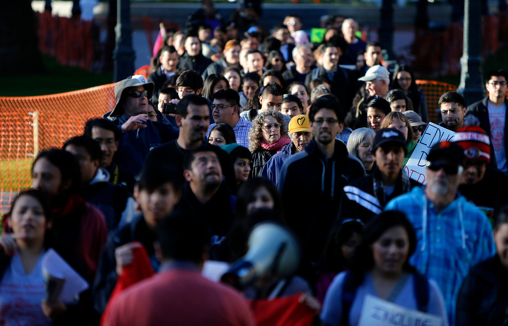 ". Protestors march through Plaza De Cesar Chavez during an ""Immigration Reform Now\"" rally in San Jose, Calif., on Thursday, Feb. 21, 2013.  They were protesting comprehensive immigration reform.  They began at Dr. Martlin Luther King, Jr. Library and ended at the Robert F. Peckham Federal Building.  (Nhat V. Meyer/Staff)"