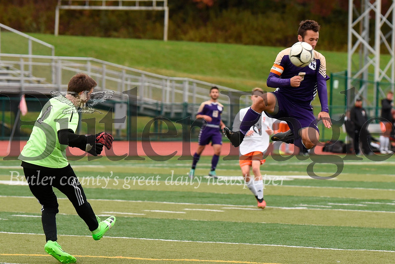 Karns City's Dakota King jumps to block a clear kick by Harbor Creek goalie Trevor Baker. King briefly left the game following the block, and later scored on a penalty kick in the second half to put the Gremlins up 3-1. Seb Foltz/Butler Eagle