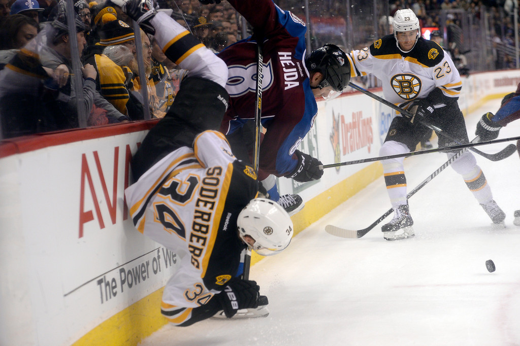 . DENVER, CO - JANUARY 21: Colorado Avalanche defenseman Jan Hejda (8) upends Boston Bruins center Carl Soderberg (34) along the boards during overtime January 21, 2015 at Pepsi Center. (Photo By John Leyba/The Denver Post)