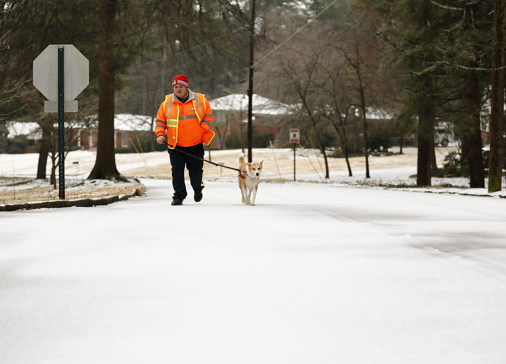 . Professional pet sitter Edward Forrester walks a neighbor\'s dog during a severe winter storm in Avondale Estates, Georgia, USA, 12 February 2014. Ice and snow in the metro Atlanta area and north Georgia is expected to make travel treacherous and cut electricity to thousands of customers.  EPA/ERIK S. LESSER