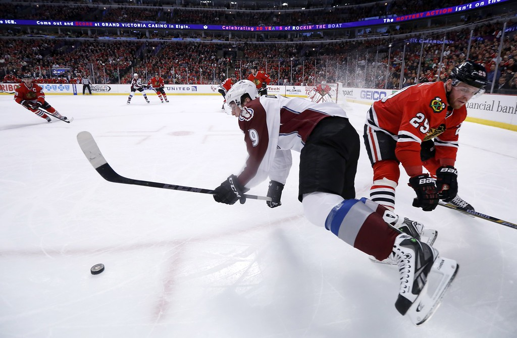. Chicago Blackhawks left wing Bryan Bickell (29) checks Colorado Avalanche center Matt Duchene (9) near the boards during the first period of an NHL hockey game Tuesday, Jan. 6, 2015, in Chicago. (AP Photo/Charles Rex Arbogast)