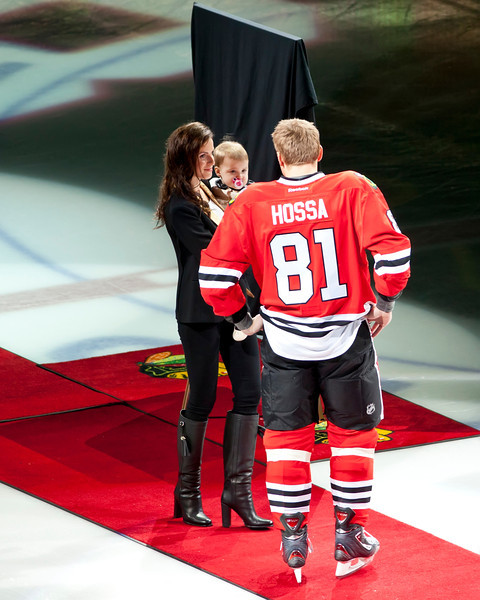Marion Hossa greeting his wife and daughter during a ceremony celebrating his 1000th NHL game.