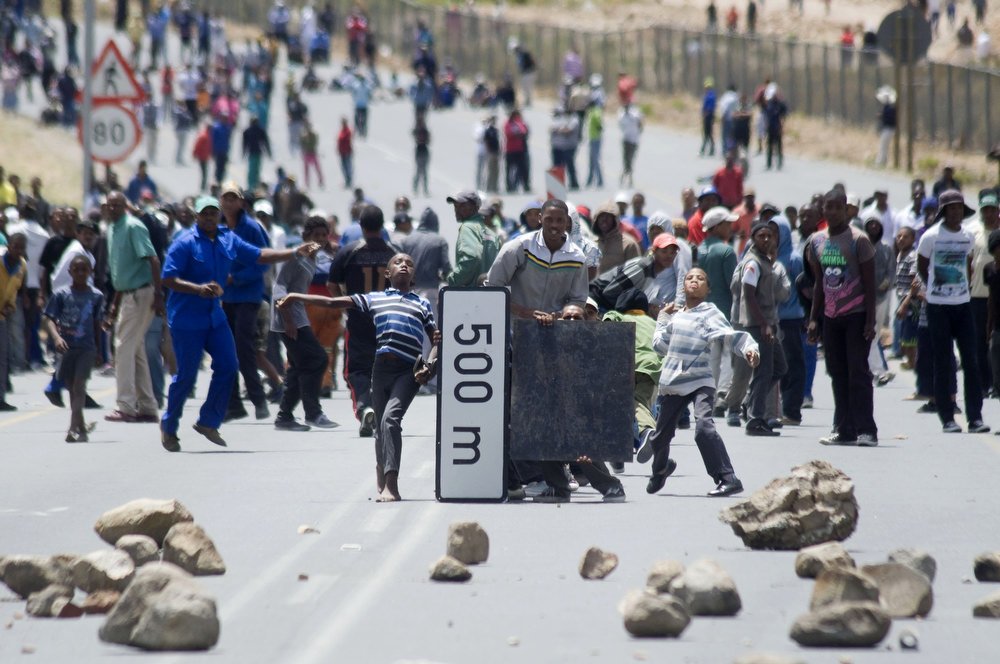 Description of . Striking farmworkers and other protestors throw stones, while hiding behind broken road signs during violent clashes with members of the South African Police Services(not visible), on January 10, 2012 in de Doorns, a small farming town about 140Km North of Cape Town, South Africa. The farm workers have said that they they will not return to work on the fruit growing region's farms until they receive a daily wage of at least R150($17) per day, which is about double what they currently earn.  AFP PHOTO / RODGER  BOSCH/AFP/Getty Images