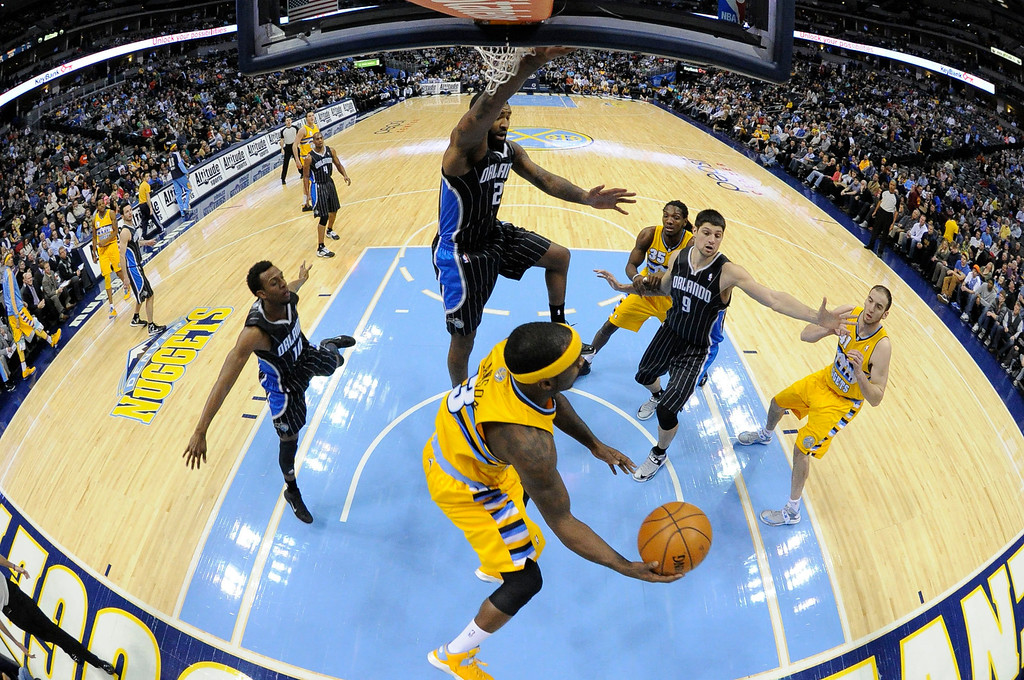 . Denver Nuggets point guard Ty Lawson (3) drives under the basket on Orlando Magic power forward Kyle O\'Quinn (2) during the first quarter Wednesday, January 9, 2013 at Pepsi Center. John Leyba, The Denver Post