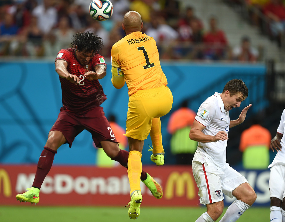 . Portugal\'s Bruno Alves, left, and United States\' goalkeeper Tim Howard battle for the ball during the group G World Cup soccer match between the USA and Portugal at the Arena da Amazonia in Manaus, Brazil, Sunday, June 22, 2014. (AP Photo/Paulo Duarte)