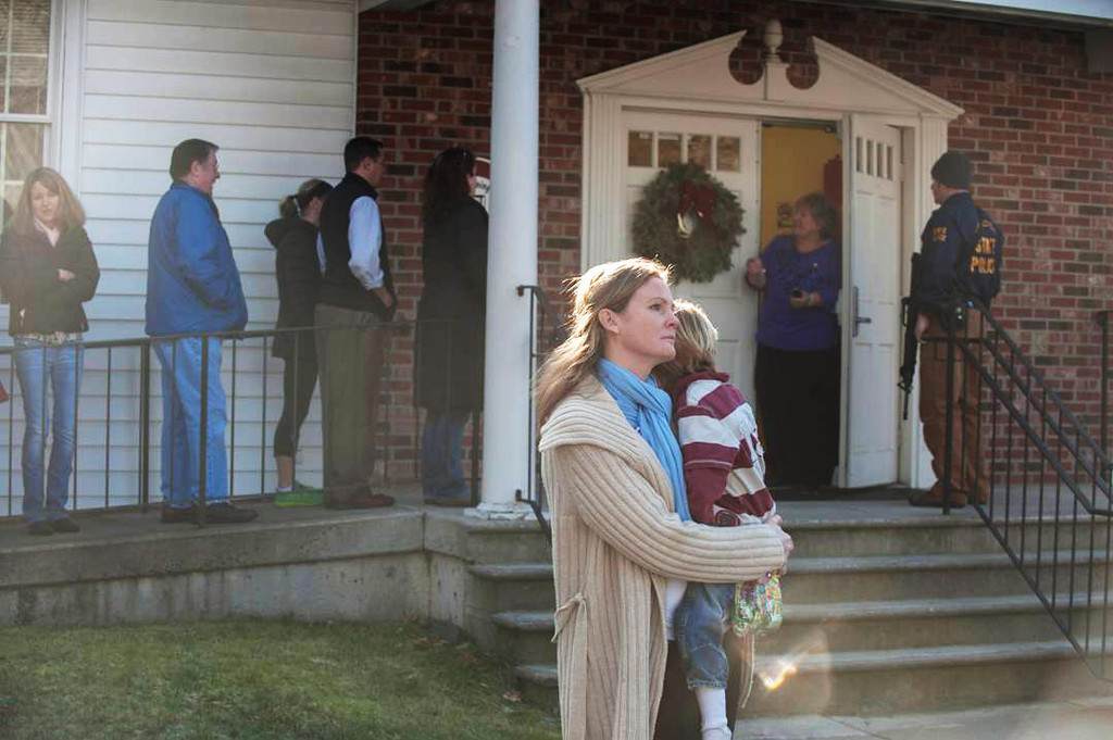 . NEWTOWN, CT - DECEMBER 14:  A woman holds a child as people line up to enter the Newtown Methodist Church near the the scene of an elementary school shooting on December 14, 2012 in Newtown, Connecticut. According to reports, there are about 27 dead, 18 children, after a gunman opened fire in at the Sandy Hook Elementary School. The shooter was also killed.  (Photo by Douglas Healey/Getty Images)