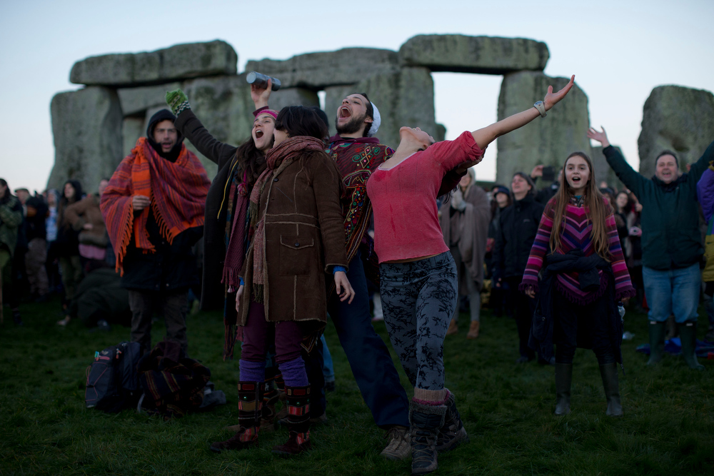 Description of . People react as they see the sun starting to rise on the horizon before its light hits them by the ancient stone circle of Stonehenge, in southern England, as access to the site is given to druids, New Age followers and members of the public on the annual Winter Solstice, Friday, Dec. 21, 2012.  Doomsday hour is here and so still are we.  According to legend, the ancient Mayans' long-count calendar ends at midnight Thursday, ushering in the end of the world. Didn't happen.