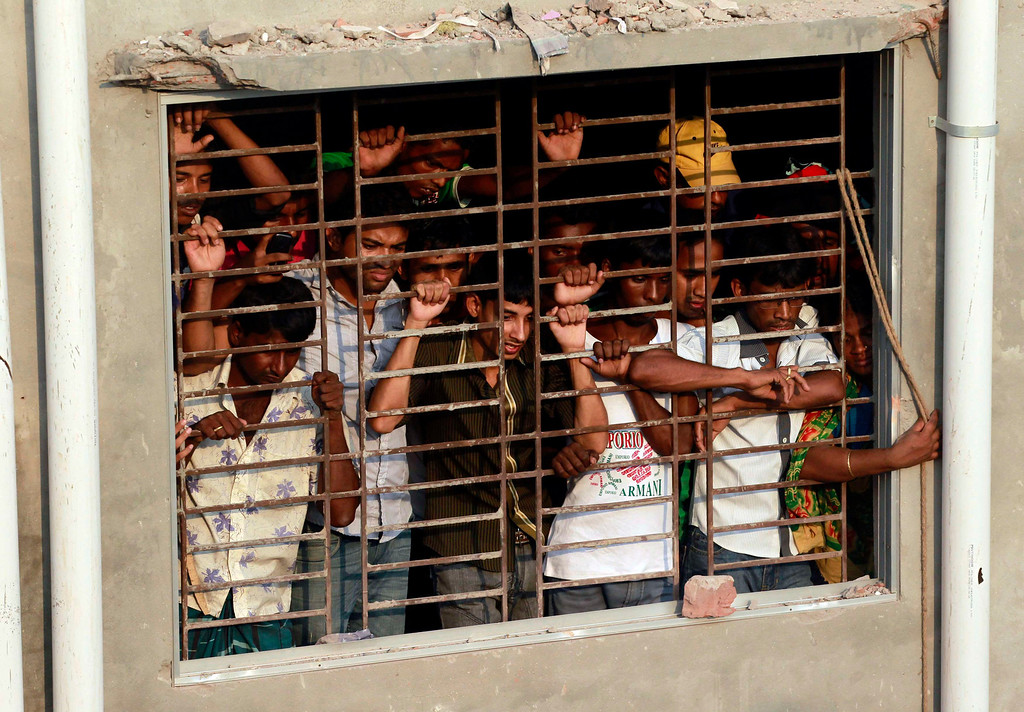 . People watch rescue operations after the Rana Plaza building collapsed, in Savar, 30 km (19 miles) outside Dhaka April 24, 2013.REUTERS/Andrew Biraj