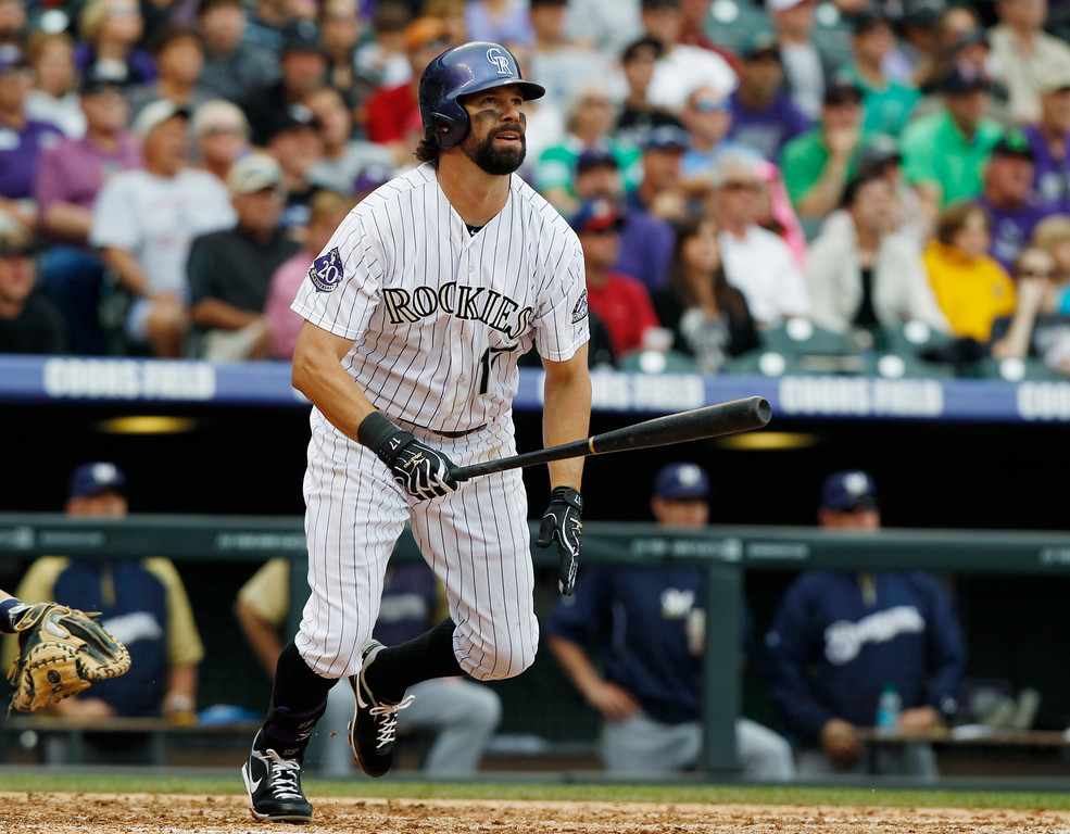 . Colorado Rockies\' Todd Helton follows the flight of his triple against the Milwaukee Brewers in the fourth inning of a baseball game in Denver, Sunday, July 28, 2013. (AP Photo/David Zalubowski)