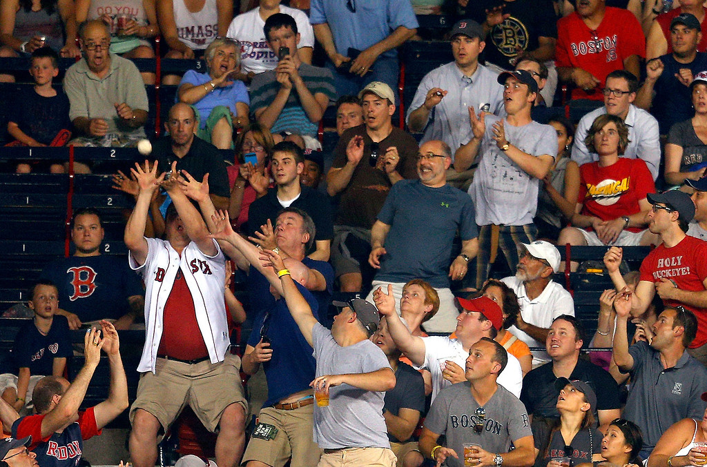 . A fan makes a play for a you ball during a game between the Boston Red Sox and Colorado Rockies at Fenway Park on June 25, 2013 in Boston, Massachusetts.  (Photo by Jim Rogash/Getty Images)