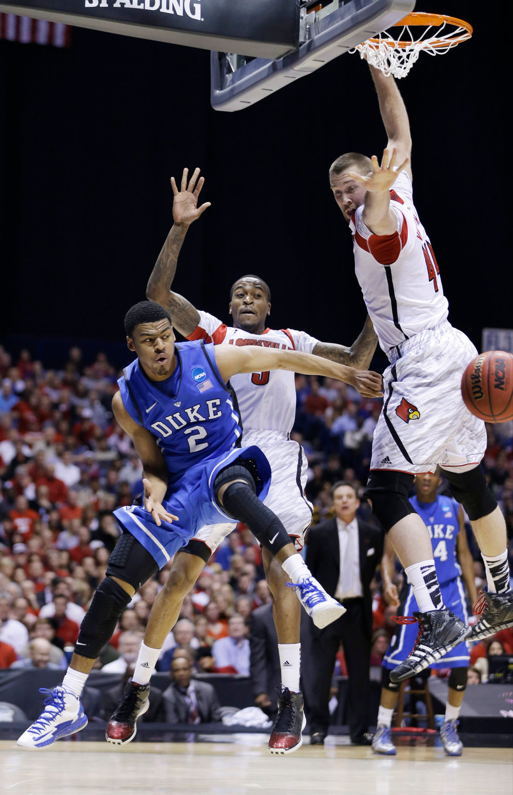 Description of . Duke's Quinn Cook (2) passes the ball against Louisville's Stephan Van Treese (44) and Kevin Ware (5) during the first half of the Midwest Regional final in the NCAA college basketball tournament, Sunday, March 31, 2013, in Indianapolis. (AP Photo/Darron Cummings)
