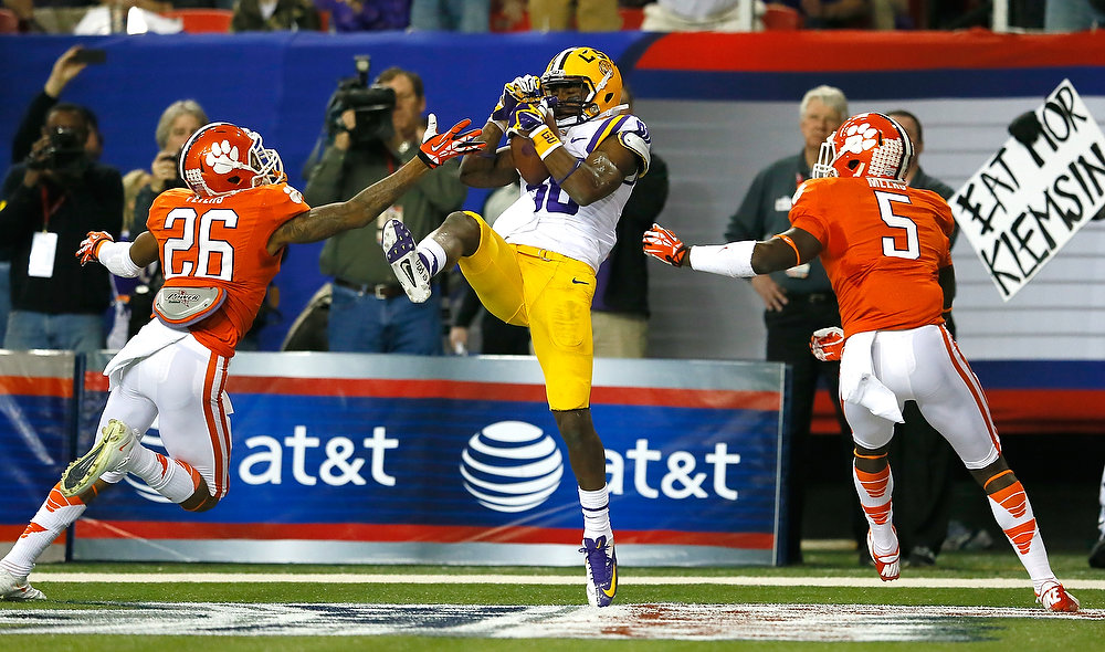 Description of . Jarvis Landry #80 of the LSU Tigers pulls in this touchdown reception against the Garry Peters #26 and Jonathan Meeks #5 of the Clemson Tigers during the 2012 Chick-fil-A Bowl at Georgia Dome on December 31, 2012 in Atlanta, Georgia.  (Photo by Kevin C. Cox/Getty Images)