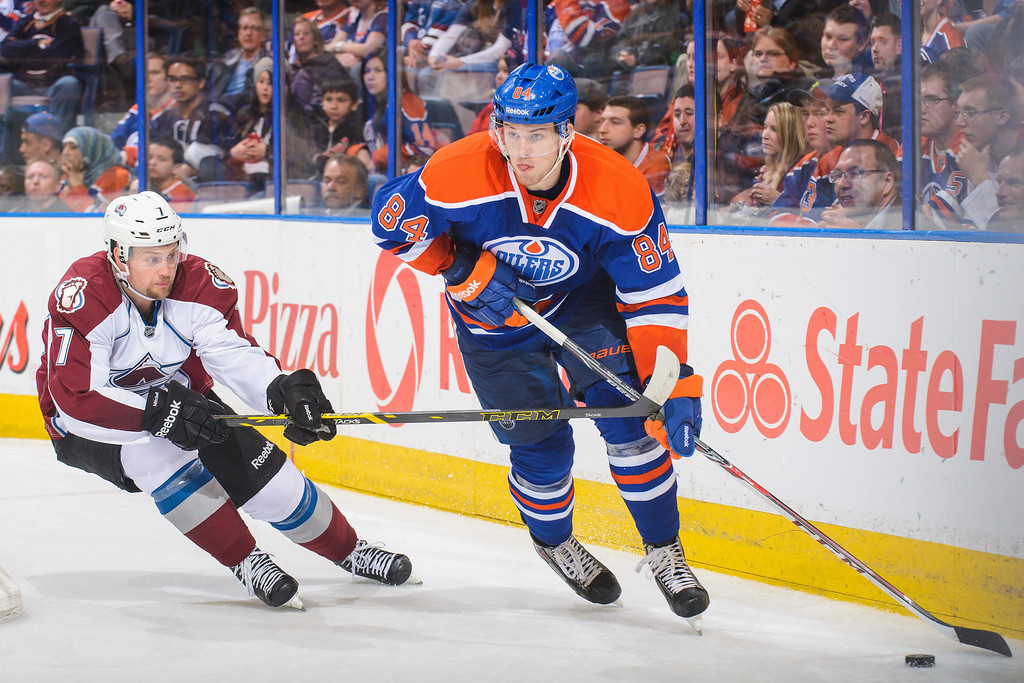 . Oscar Klefbom #84 of the Edmonton Oilers skates with the puck against John Mitchell #7 of the Colorado Avalanche during an NHL game at Rexall Place on April 8, 2014 in Edmonton, Alberta, Canada. The Avalanche defeated the Oilers 4-1. (Photo by Derek Leung/Getty Images)