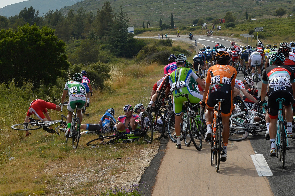 . Jerome Coppel of France, left in red jersey, crashes during the fifth stage of the Tour de France cycling race over 228.5 kilometers (142.8 miles) with start in Cagnes-sur-Mer and finish in Marseille, southern France, Wednesday July 3, 2013. (AP Photo/Jerome Prevost/L\'Equipe, POOL)