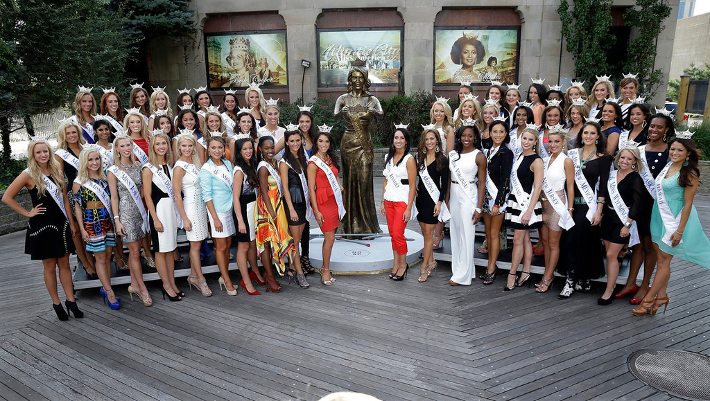 . Miss America contestants pose with a statue after arriving in Atlantic City, N.J. on Tuesday, Sept. 3, 2013. The Miss America pageant is back in the city where it began, six years after spurning the city for Las Vegas. The pageant held a welcoming ceremony Tuesday for the 53 contestants, one from each state plus the District of Columbia, Puerto Rico and the U.S. Virgin n Islands. The contestants filed out of Boardwalk Hall, where the competition will begin next week and culminate days later, and walked across the Boardwalk to a stage. (AP Photo/Mel Evans)