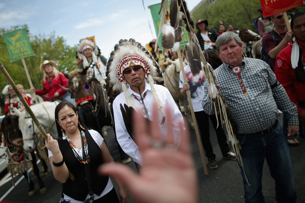 ". Members of the Cowboy and Indian Alliance, including Native Americans, farmers and ranchers from across the United States, march down Independence Avenue while demonstrating against the proposed Keystone XL pipeline April 22, 2014 in Washington, DC. As part of its ""Reject and Protect\"" protest, the Cowboy and Indian Alliance is organizing a weeklong series of actions by farmers, ranchers and tribes to show their opposition to the pipeline.  (Photo by Chip Somodevilla/Getty Images)"